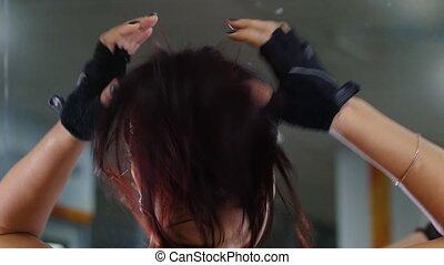 A young woman putting her hair on ponytail. Gym.
