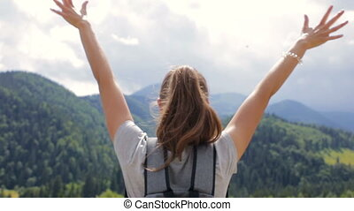 A young woman raise their hands up for joy.