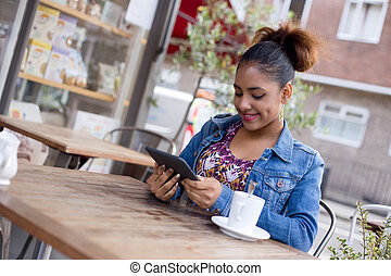 coffee shop - a young woman reading a book at the coffee...