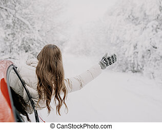 A young woman rejoices at the coming of winter. Winter forest.
