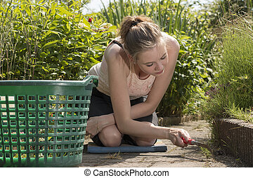young woman removes weeds from her garden