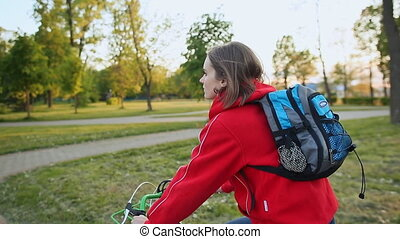 A young woman rides a bicycle with blue backpack