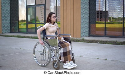 A young woman rides a wheelchair and a heart attack occurs. A girl in a wheelchair against the background of a glass building grabs her heart. Special transport for the disabled. 4k