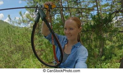 A young woman rides a zip line in an adventure park. She wears a safety harness. Outdoor amusement center with climbing activities consisting of zip lines and all sorts of obstacles. Slowmotion video.