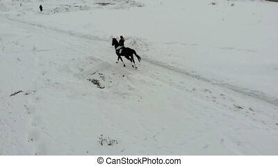 A young woman riding a horse on a snowy field in a village....