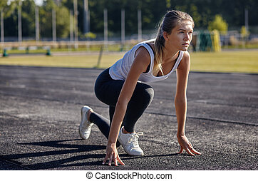 a young woman runner getting ready for a run on track