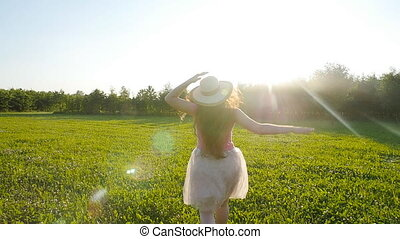 A young woman runs along a green glade at sunset