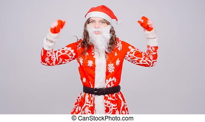 A young woman Santa Claus is dancing