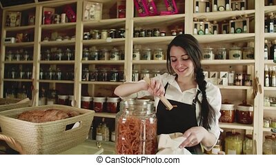 A young woman shop assistant working in a zero-waste store or shop.