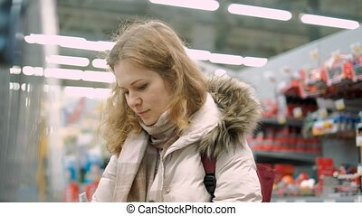A young woman shopping chooses the goods in the supermarket...