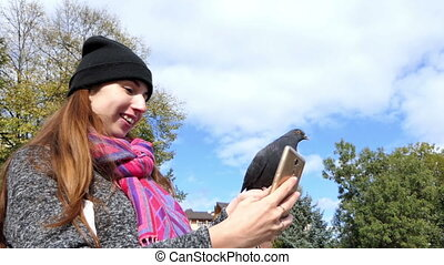 A young woman shots a dove sitting on her hand with her mobile in slo-mo