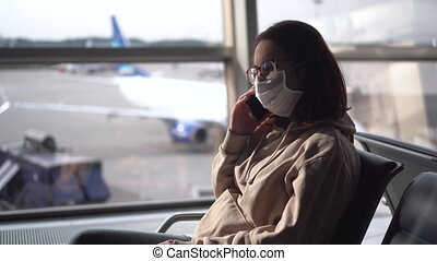 A young woman sits and speaks on the phone against the background of a window at the airport. Airplanes in the background.