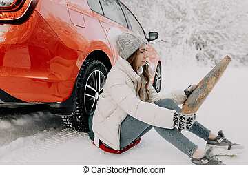 A young woman sits by a red car and holds a map in her hands. Travel concept.