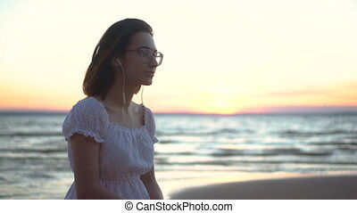 A young woman sits on a stone on the beach by the sea with headphones in her ears. A girl in a white dress at sunset listens to music on headphones closeup.