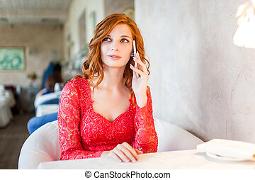 A young woman sitting in a cafe with cell phone