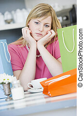 A young woman sitting in a cafe with shopping bags
