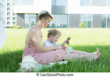 A young woman sitting in the grass. A child is sitting next to her. They play with toys.