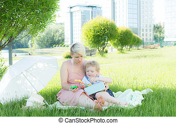 A young woman sitting in the grass. A child is sitting next to her. They play with toys. Next to it is a white umbrella