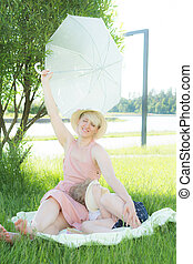 A young woman sitting in the grass. A child sleeps in her lap. she is holding a white umbrella