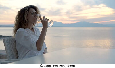 A young woman sitting on the beach and meets a sunset with a glass of wine in her hand