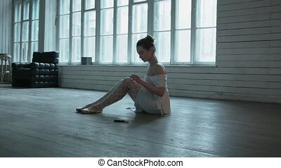 A young woman sitting on the floor takes a marker and draws them on the shoes. Beautiful blonde on a wooden floor with tights in a large mesh and white dress. Hair blonde swirling in a bagel.