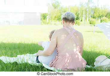 A young woman sitting on the grass. a child is sitting next to her. The view from the back