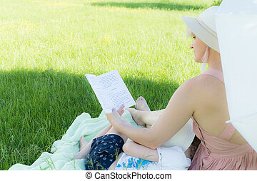 A young woman sitting on the grass. A child sleeps in her lap. She's reading a book. she holds a white umbrella