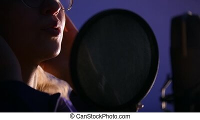 A young woman standing by the mic and recording a song in the studio. Mid shot