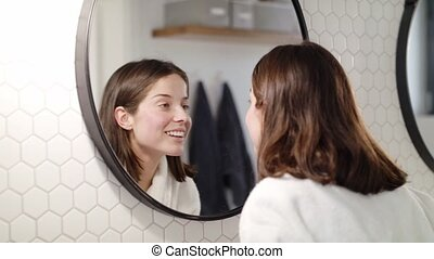 A young woman standing indoors in bathroom at home looking in mirror.