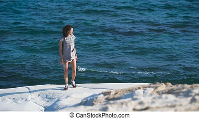 A young woman standing near by the sea in the long t-shirt