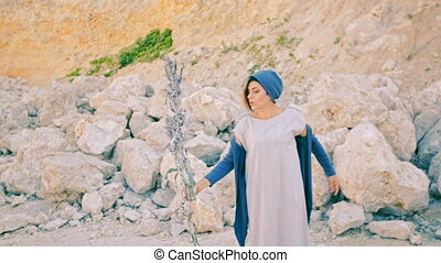 A young woman stands against a background of mountains and...