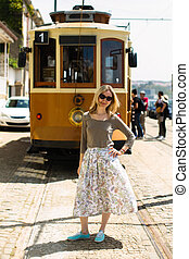 A young woman stands near the an old tram.