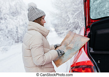 A young woman stands next to a red car and holds a map in her hands. Travel concept.