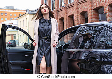 young woman stands next to her car in the Parking