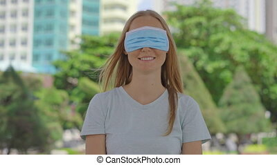 A young woman stands on a street. She is wearing a medical face mask in the wrong way. Her mask does not cover her mouth, instead, it covers her eyes. Wrong-way of using a face mask