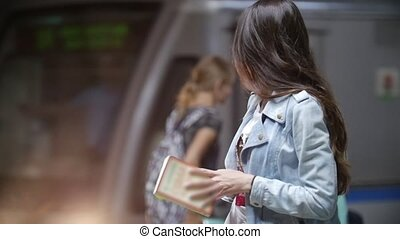 A young woman straightens her hair in the subway, slow motion