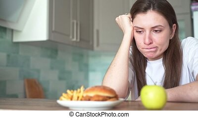 A young woman suffers because of the choice of food between harmful and healthy. The temptation to eat a hamburger with fried fries, dieting slowmo