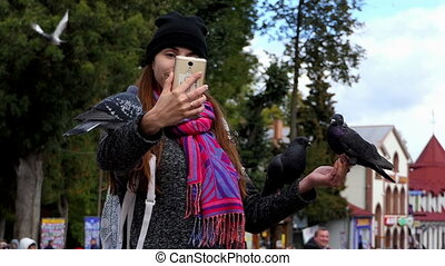 A young woman takes a selfie with doves on her arms in slo-mo