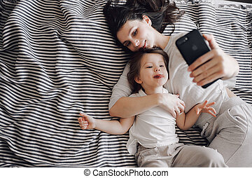a young woman takes a selfie with her little daughter on the striped coat