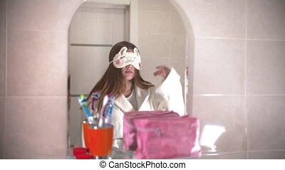 A young woman takes off her sleeping mask and look at herself in the mirror