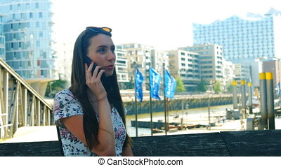 A young woman talking on a smartphone and laughing