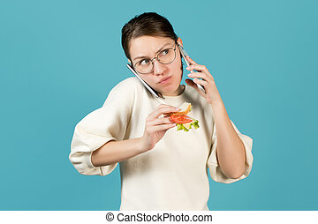 A young woman talking on two phones at once while eating