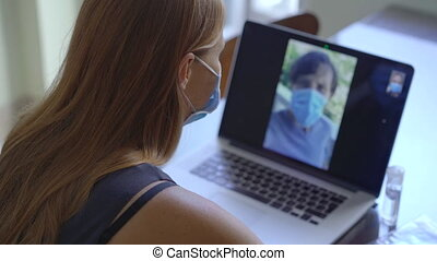 A young woman talks through video conferencing while she is sitting at home during the coronavirus self-isolation period. Social distancing concept.