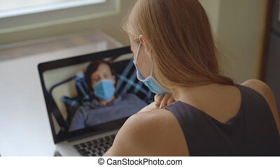 A young woman talks through video conferencing while she is sitting at home during the coronavirus self-isolation period. Social distancing concept