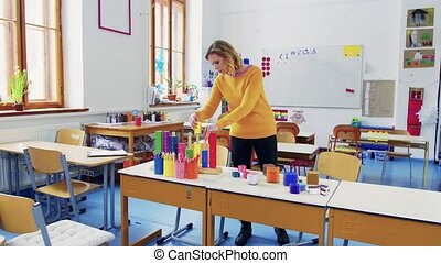 A young woman teacher in the classroom at school.