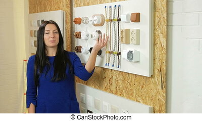 A young woman tells and shows the switch sockets and wires of different colors and shapes. Samples are presented on a special stand. Looking at the camera