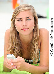 A young woman texting on the beach.