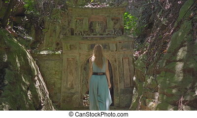 A young woman tourist visits the The Marble mountains a complex of Buddhist temples, famous tourist destination in the city of Da Nang, central Vietnam. She walks through old gates to the biggest cave temple. Travel to Vietnam concept.