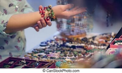 A young woman tries on bracelets on the market