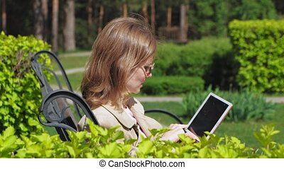 A young woman uses a computer tablet. Remote business concept